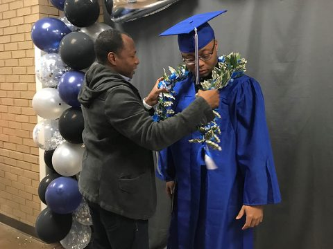 During the filming of the Fort Campbell High School 2020 Graduation Ceremony May 6 at FCHS, Sgt. 1st Class Willie Williams, places a money lei on his son, Kamari, graduating senior. Williams is a Soldier assigned to Headquarters and Headquarters Company, 3rd Brigade Combat Team, 101st Airborne Division (Air Assault) (Stephanie Ingersoll, Fort Campbell Courier).