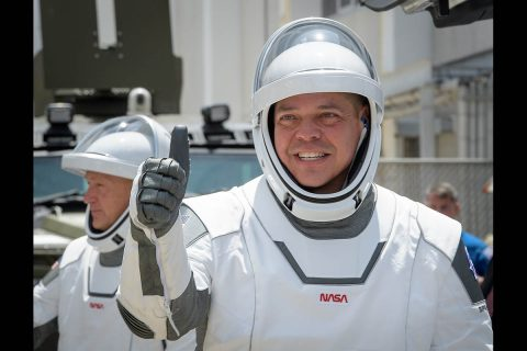NASA astronauts Robert Behnken, foreground, and Douglas Hurley, wearing SpaceX spacesuits, are seen as they depart the Neil A. Armstrong Operations and Checkout Building for Launch Complex 39A to board the SpaceX Crew Dragon spacecraft for the Demo-2 mission launch, Saturday, May 30, 2020, at NASA's Kennedy Space Center in Florida. (NASA/Bill Ingalls)