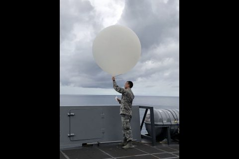 Senior Airman Kyle Boyes of the U.S. Air Force's 45th Weather Squadron out of Patrick Air Force Base in Florida releases a weather balloon during Underway Recovery Test-8 in the Pacific Ocean in March 2020. (NASA/Amanda Griffin)