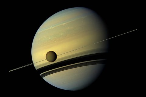 Larger than the planet Mercury, huge moon Titan is seen here as it orbits Saturn. Below Titan are the shadows cast by Saturn's rings. This natural color view was created by combining six images captured by NASA's Cassini spacecraft on May 6, 2012. (NASA/JPL-Caltech/Space Science Institute)