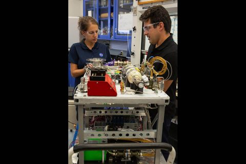 Annie Meier, left, and Jamie Toro assemble the flight hardware for the Orbital Syngas/Commodity Augmentation Reactor (OSCAR) in the Space Station Processing Facility at NASA's Kennedy Space Center in Florida. (NASA/Cory Huston)