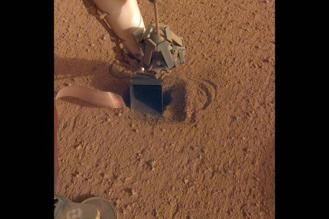 "The movement of sand grains in the scoop on the end of NASA InSight's robotic arm suggests that the spacecraft's self-hammering ""mole,"" which is in the soil beneath the scoop, had begun tapping the bottom of the scoop while hammering on June 20, 2020. (NASA/JPL-Caltech)"