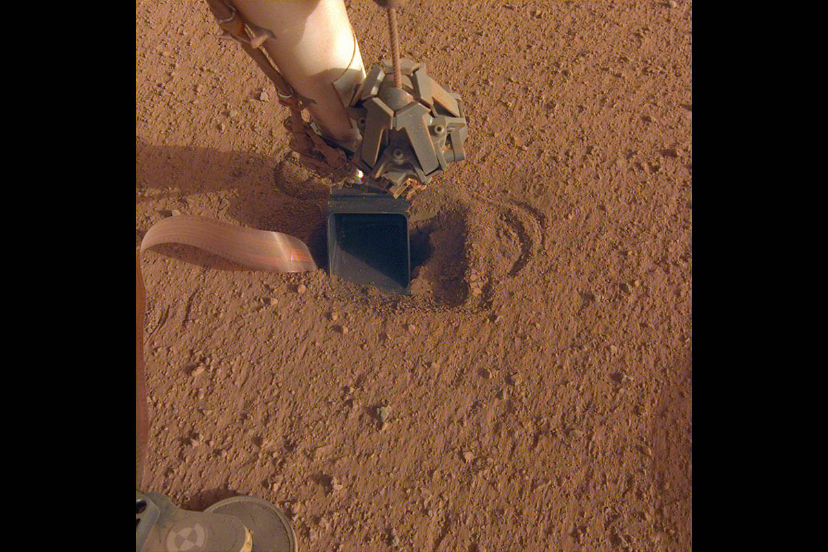 The movement of sand grains in the scoop on the end of NASA InSight's robotic arm suggests that the spacecraft's self-hammering