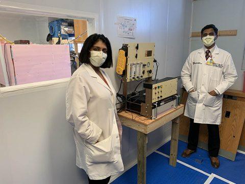 Doctors Amrita John and Shine Raju at UH Cleveland Medical Center with the device that decontaminates masks using atomic oxygen. (University Hospitals)