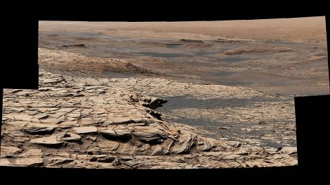 "Stitched together from 28 images, NASA's Curiosity Mars rover captured this view from ""Greenheugh Pediment"" on April 9, 2020, the 2,729th Martian day, or sol, of the mission. In the foreground is the pediment's sandstone cap. At center is the ""clay-bearing unit""; the floor of Gale Crater is in the distance. (NASA/JPL-Caltech/MSSS)"