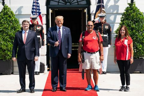 "President Donald Trump, Veterans Affairs Secretary Robert Wilkie, and Second Lady Karen Pence with U.S. Marine Terry Sharpe, the ""Walking Marine"". (White House)"