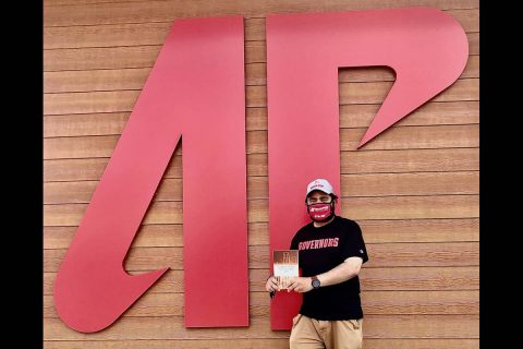 Austin Peay State University professor Somaditya Banerjee poses outside the new Ann R. Ross Bookstore with his book. (APSU)