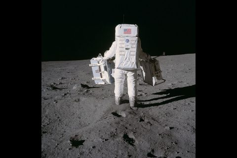 Astronaut Edwin E. Aldrin Jr., lunar module pilot, deploys two components of the Early Apollo Scientific Experiments Package on the surface of the Moon during the Apollo 11 extravehicular activity in 1969. A seismic experiment is in his left hand, and in his right is a laser-reflecting panel. Astronaut Neil A. Armstrong, mission commander, took this photograph. (NASA's Johnson Space Flight Center)