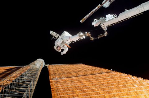 """Astronaut Scott Parazynski, while anchored to a foot restraint, assessed his repair work as the solar array was fully deployed while Space Suttle Discovery was docked with the International Space Station. Astronaut Doug Wheelock (out of frame) assisted from the truss by keeping an eye on the distance between Parazynski and the array. (Doug """"Wheels"""" Wheelock)"""