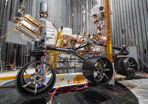 The NASA Ingenuity Mars Helicopter can be seen between the left and center wheels of the Mars 2020 Perseverance rover. The image was taken in the vacuum chamber at JPL on October 1st, 2019. (NASA/JPL-Caltech)