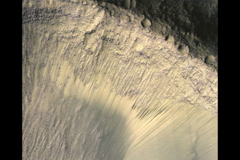 This image from the High Resolution Imaging Science Experiment (HiRISE) camera on NASA's Mars Reconnaissance Orbiter show how the appearance of dark markings on Martian slope changes with the seasons. The marks, called recurrent slope linea, extend down slopes during warmer months and fade away during cooler months. (NASA/JPL-Caltech/Univ. of Arizona)