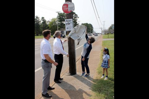 Immaculate Conception School Principal Stephanie Stafford and student Amelia Campagna help CTS Director Paul Nelson and Clarksville Mayor Joe Pitts unveil the Adopt-A-Stop sign at the CTS bus stop in front of the school.