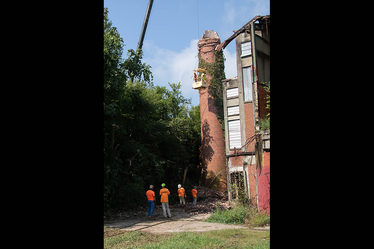 Workers inspect the structure after the top half of the smokestack came down. After a second pull by a bulldozer, the bottom half toppled, becoming a pile of dust and rubble.
