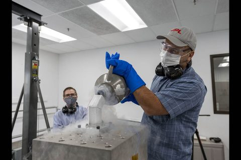 "Andrew Kennett (left) watches as Dominic Aldi (right) uses liquid nitrogen to cool a motor integrated bulk metallic glass gearbox prior to shock testing it. The motor and gearbox are inside the frosty metal ""bucket"" that contains the liquid nitrogen. The tooling, including the ""bucket"" is designed to be mounted both vertically (shown) and horizontally on the cube for testing the motor and gearbox in three orientations. (NASA/JPL-Caltech)"