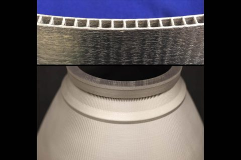 Complex designs – such as engine nozzles with integrated channels walls – can be fabricated using blown powder directed energy deposition. The sides of the nozzle and channel walls above are only the thickness of a few pieces of notebook paper. (NASA)