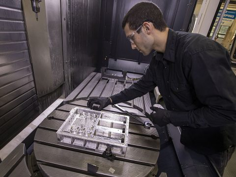 Langley engineer John Savage inspects a section of the navigation Doppler lidar unit after its manufacture from a block of metal. (NASA/David C. Bowman)