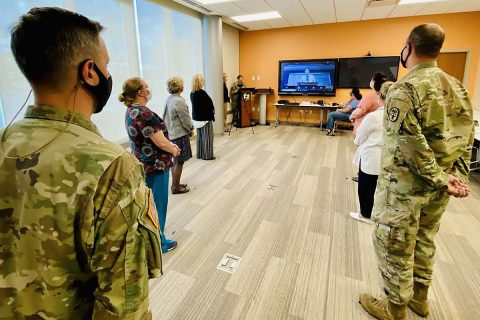 Blanchfield Army Community Hospital Commander Col. Patrick T. Birchfield (left) listens as Army Medicine Chief of Staff and Chief of the Army Medical Department Civilian Corps Mr. Richard Beauchemin praises the team of gathered BACH Soldiers and Department of the Army Civilians for their innovative process-improvement initiative to streamline patient access to behavioral health resources within the hospital's primary care clinics.