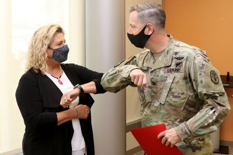 Blanchfield Army Community Hospital Commander Col. Patrick T. Birchfield gives an elbow bump to BACH's Screaming Eagle Medical Home Behavioral Health Consultant Ms. Joan Lovett before presenting her the Commander's Certificate of Achievement for her contributions to the behavioral health team. Lovett participated in an award-winning process-improvement initiative to streamline patient access to behavioral health resources within the hospital's primary care clinics to enhance patient outcomes and medical readiness.