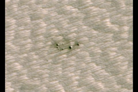 The HiRISE camera aboard NASA's Mars Reconnaissance Orbiter took this image of a crater cluster on Mars, the first ever to be discovered AI. The AI first spotted the craters in images taken the orbiter's Context Camera; scientists followed up with this HiRISE image to confirm the craters. (NASA/JPL-Caltech/University of Arizona)