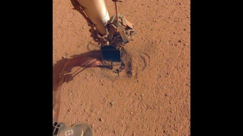 """NASA's InSight retracted its robotic arm on Oct. 3, 2020, revealing where the spike-like """"mole"""" is trying to burrow into Mars. The copper-colored ribbon attached to the mole has sensors to measure the planet's heat flow. In the coming months, the arm will scrape and tamp down soil on top of the mole to help it dig. (NASA/JPL-Caltech)"""