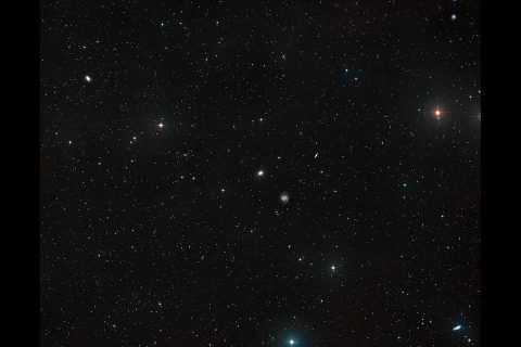 New data from the NASA/ESA Hubble Space Telescope provides further evidence for tidal disruption in the galaxy NGC 1052-DF4. This result explains a previous finding that this galaxy is missing most of its dark matter. By studying the galaxy's light and globular cluster distribution, astronomers have concluded that the gravitational forces of the neighboring galaxy NGC 1035 stripped the dark matter from NGC 1052-DF4 and are now tearing the galaxy apart. (ESA/Hubble, NASA, Digitized Sky Survey 2; Acknowledgment: Davide de Martin)