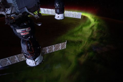 "From the International Space Station's orbit 269 miles above the Indian Ocean southwest of Australia, this nighttime photograph captures the aurora australis, or ""southern lights."" Russia's Soyuz MS-12 crew ship is in the foreground and Progress 72 resupply ship in the background. (NASA)"