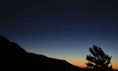 "Saturn, top, and Jupiter, below, are seen after sunset from Shenandoah National Park, Sunday, Dec. 13, 2020, in Luray, Virginia. The two planets are drawing closer to each other in the sky as they head towards a ""great conjunction"" on December 21, where the two giant planets will appear a tenth of a degree apart. (NASA/Bill Ingalls)"