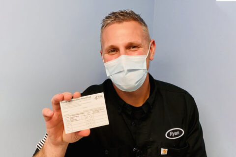 Registered nurse, Mr. Ryan Diehl, a frontline healthcare worker assigned to Blanchfield Army Community Hospital's Emergency Center, shows his COVID-19 Vaccination Record Card before adding his personal information. He and other healthcare workers and first responders are among the first recipients of the first phase of COVID vaccines on Fort Campbell. (U.S. Army photo by Maria Yager)