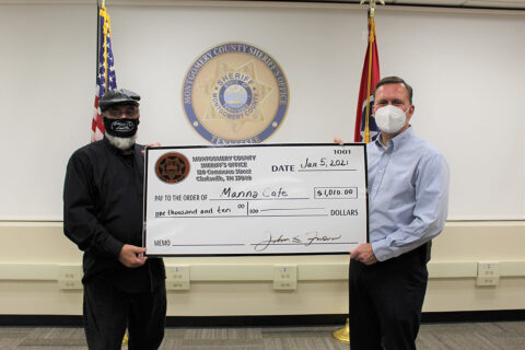 Manna Cafe Ministries founder Kenny York accepts check from Montgomery County Sheriff John Fuson.