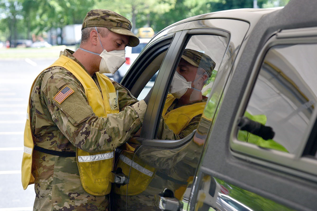 Sgt. Zack Vredenburgh, from Clarksville, administers a COVID-19 vaccine at the drive-thru testing and vaccination center at Volunteer State Community College, May 13th, in Gallatin. (1st Class William Jones, Tennessee National Guard Public Affairs Office)