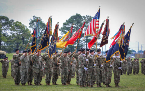 Unit commanders and colour bearers salute during a change of command ceremony for the 3rd Brigade Combat Team, 101st Airborne Division (Air Assault), on Fort Campbell, KY June 18th, 2021. The unit colours is passed during a ceremony which symbolizes the transfer of command responsibility and authority from the old commander to the new commander. (Staff Sgt. Michael Eaddy)