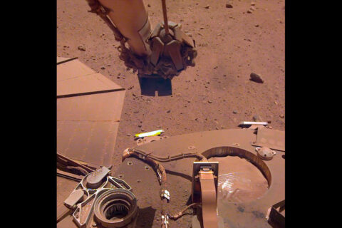 To clean a bit of dust from one of its solar panels, NASA's InSight lander trickled sand above the panel. The wind-borne sand grains then picked up some dust on the panel, enabling the lander to gain about 30 watt-hours of energy per sol on May 22nd, 2021, the 884th Martian day of the mission. (NASA/JPL-Caltech)