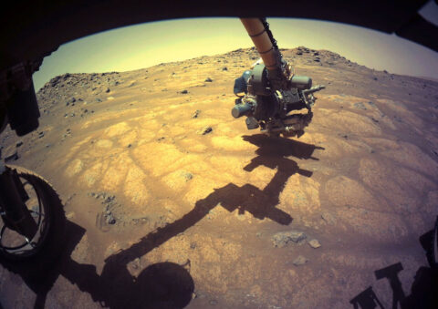 """The robotic arm on NASA's Perseverance rover reached out to examine rocks in an area on Mars nicknamed the """"Cratered Floor Fractured Rough"""" area in this image captured on July 10th, 2021 (the 138th sol, or Martian day, of its mission). (NASA/JPL-Caltech)"""