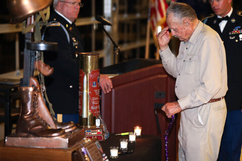 Mr. Dan McBride, a WWII veteran and a member of The Rakkasan Association, salutes during a candle lighting portion of a memorial dinner at the Wilma Rudolph Event Center in Clarksville, Tennessee, during a week's long reunion on Fort Campbell June 24th, 2021. (Staff Sgt. Michael Eaddy)