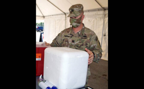 Capt. Gregg Murphy, a transportation officer with Memphis' 1172nd Transportation Company, sets up a COVID-19 vaccination station in Carthage on May 22nd. (Sgt. Finis L. Dailey, III)