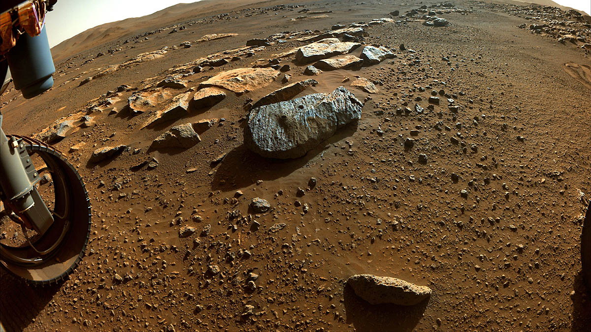 """Two holes are visible in the rock, nicknamed """"Rochette,"""" from which NASA's Perseverance rover obtained its first core samples. The rover drilled the hole on the left, called """"Montagnac,"""" on Sept. 7, and the hole on the right, known as """"Montdenier,"""" on Sept. 1. Below it is a round spot the rover abraded. (NASA/JPL-Caltech)"""